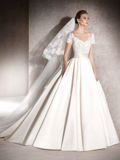 Красивое свадебное платье очаровывает широкой юбкой «принцесса» с пышными вертикальными волнами ткани и эксцентричными скрытыми карманами. Платье нежно облегает талию, силуэт подчеркнут широким атласным поясом. Изящный открытый корсет с лифом в форме сердечка покрыт шантильским кружевом, которое создает фигурный V-образный вырез и короткие рукава. На спинке кружево очерчивает округлое декольте.
