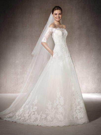 Романтичное свадебное платье с великолепной юбкой классического А-силуэта эксцентрично дополнено скрытыми карманами по верху подола. Верх, оформленный шантильским кружевом, подчеркивает плечи выразительным портретным декольте с полупрозрачными рукавами длиной до локтя. Завершает образ роскошный полукруг длинного шлейфа из тонкой ткани, дополненной крупными кружевными аппликациями.
