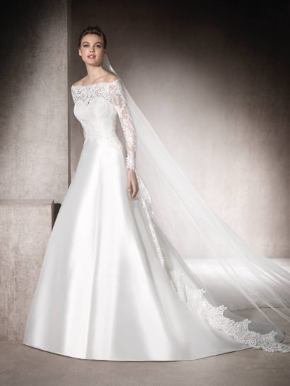 Впечатляющее свадебное платье «принцесса» создано из сверкающего шелка микадо. Широкая юбка подчеркивает талию. Отделка тонким тюлем и кружевом усиливает эффект. Кружевная ткань покрывает и лиф, обрамляя портретное декольте и создавая облегающие рукава с фигурными манжетами, украшенными пуговицами и бисерной вышивкой. Деликатный глянцевый шлейф служит изящным завершением образа.