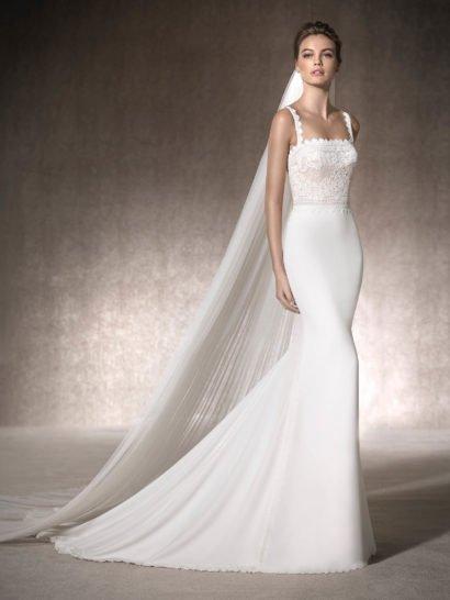 Изысканное свадебное платье чувственного кроя «русалка» выполнено в богемном стиле. Лаконичная юбка из крепа облегает бедра и образует ниже коленей великолепный шлейф, пышной волной простирающийся сзади. Корсет с прямой линией декольте выполнен в оттенке слоновой кости и украшен кружевом и гипюром. Оригинальное декольте дополняют фигурные кружевные бретели, расположенные симметрично.