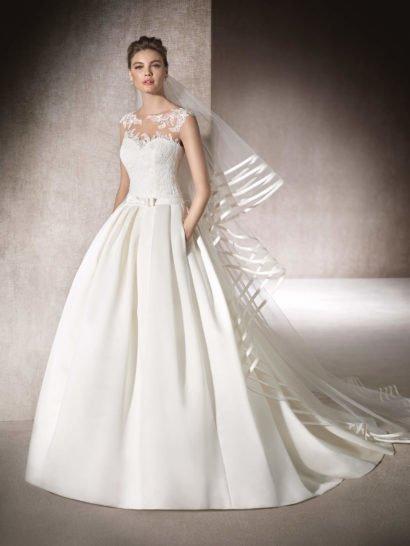 Стильное свадебное платье с юбкой из плотной ткани, украшенной вертикальными складками от талии и дополненной скрытыми карманами.  На талии – элегантный узкий пояс с женственным бантом. Корсет с лифом в форме сердца покрыт тюлем с кружевными аппликациями и бисерной вышивкой.  На спинке – соблазнительный вырез, обрамленный тонкой тканью с романтичным декором.