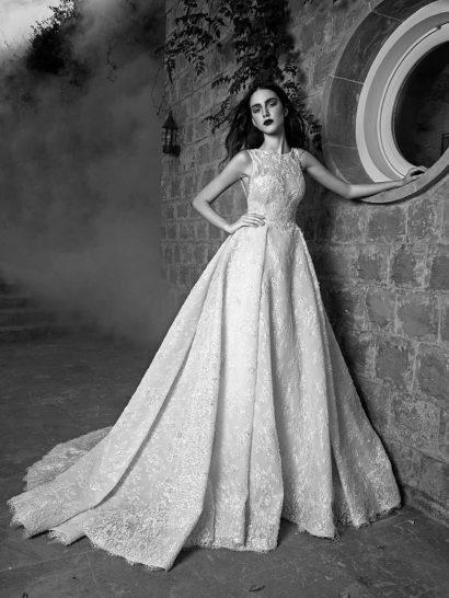 Фактурное свадебное платье создано для невесты, которой нравится покорять и очаровывать.  Роскошный пышный крой создан многослойной юбкой, украшенной вертикальными складками от линии талии и широким полукругом шлейфа.  Особенное очарование платью гарантирует декор плотным глянцевым кружевом с романтичным цветочным рисунком.  Завершает образ закрытый лиф с полупрозрачной кружевной вставкой с вырезом под горло.    Свадебные платья Zuhair Muradэксклюзивно представлены в салоне Виктория  Примерка платьев Zuhair Murad—платная