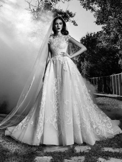 Эффектное свадебное платье с подчеркнуто пышной юбкой создает драматичный, незабываемый образ.  Многослойная юбка с пышным шлейфом сзади украшена крупным кружевным узором по всей длине, прекрасно подчеркивающим объем подола.  Кружевная отделка романтично покрывает и закрытый верх с фигурным округлым декольте и элегантными полупрозрачными бретелями, слегка приспущенными с плеч.  Свадебные платья Zuhair Muradэксклюзивно представлены в салоне Виктория