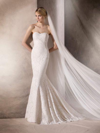 Облегающее свадебное платье с многослойной юбкой кроя «русалка» наполнено женственным настроением не только в деталях кроя с открытым лифом в форме сердечка, но и в изысканной отделке, выполненной из тонкого слоя кружева с цветочными бутонами. Сзади юбку завершает небольшой шлейф, спускающийся вертикальными складками от уровня коленей.