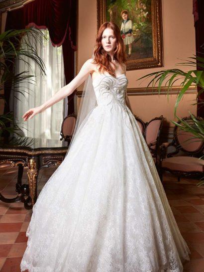 Пышное свадебное платье идеально подойдет для создания роскошного царственного образа.  Подчеркивающий фигуру открытый корсет с изящной линией декольте выразительно украшен сверкающей вышивкой, абстрактным узором из пайеток спускающейся до верха подола.  Юбка наполнена романтичным настроением благодаря верхнему слою из деликатной кружевной ткани.  Свадебные платья Yolan Crisэксклюзивно представлены в салоне Виктория  Примерка платьев Yolan Cris —платная