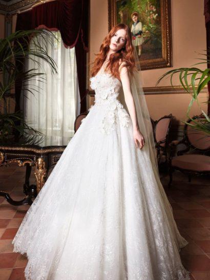 Шикарное свадебное платье бального силуэта с открытым верхом, полное утонченной элегантности.  Облегающий фигуру корсет акцентирует тонкую талию, а пышная юбка покрыта по всей длине тончайшим кружевом с мелким узором, создающим особое настроение.  Эффектная объемная отделка верха выполнена из романтичных шелковых цветов, пришитых к корсету вручную.  Свадебные платья Yolan Crisэксклюзивно представлены в салоне Виктория  Примерка платьев Yolan Cris —платная