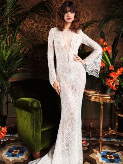 Стильное свадебное платье бохо отражает вдохновение дизайнеров эпохой семидесятых.  У платья длинная облегающая юбка и полупрозрачные рукава с выразительным зубчатым краем, расширяющиеся книзу.  Платье выполнено из эксклюзивной кружевной ткани, на которой вышивка пайетками создает геометрические узоры.  Это будет идеальный выбор для церемонии в духе ретро!  Свадебные платья Yolan Crisэксклюзивно представлены в салоне Виктория  Примерка платьев Yolan Cris —платная