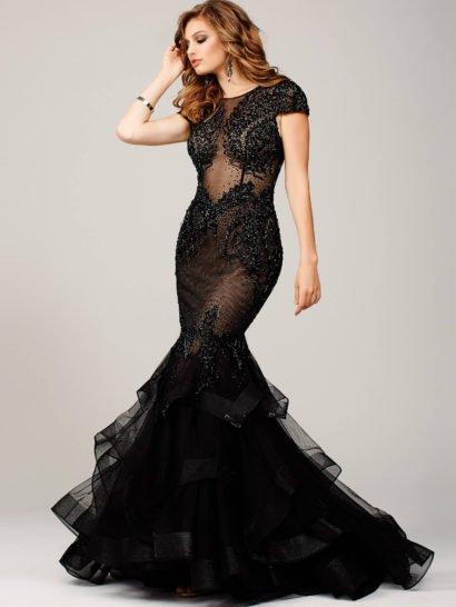 Потрясающее вечернее платье черного цвета, выполненное с иллюзией полупрозрачности. Облегающий крой позволяет эффектно продемонстрировать фигуру, а пышная юбка «русалка» из нескольких слоев легкой ткани, украшенных по краю широкими полосами тесьмы, создает торжественное настроение. На спинке – необычная застежка, создающая вертикальный ряд небольших вырезов.