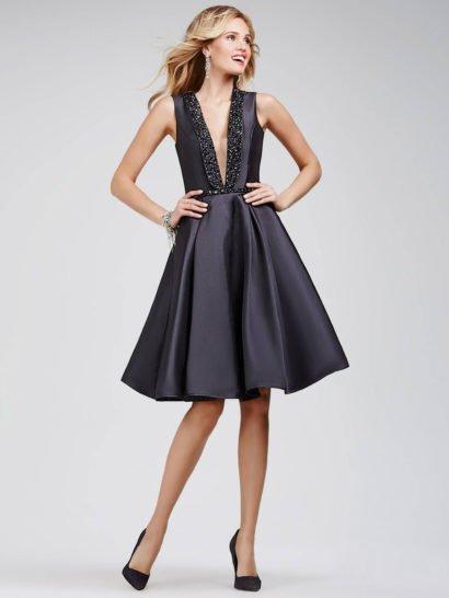 Великолепное вечернее платье с пышной юбкой А-силуэта длиной до колена создано из глянцевой черной ткани, создающей атмосферу женственной элегантности. Глубокий V-образный вырез позволяет эффектно сделать акцент на декольте, он украшен воротником, полностью покрытым крупными глянцевыми бусинами вышивки. На талии – узкий сверкающий пояс, декорированный такой же вышивкой, как и на лифе.