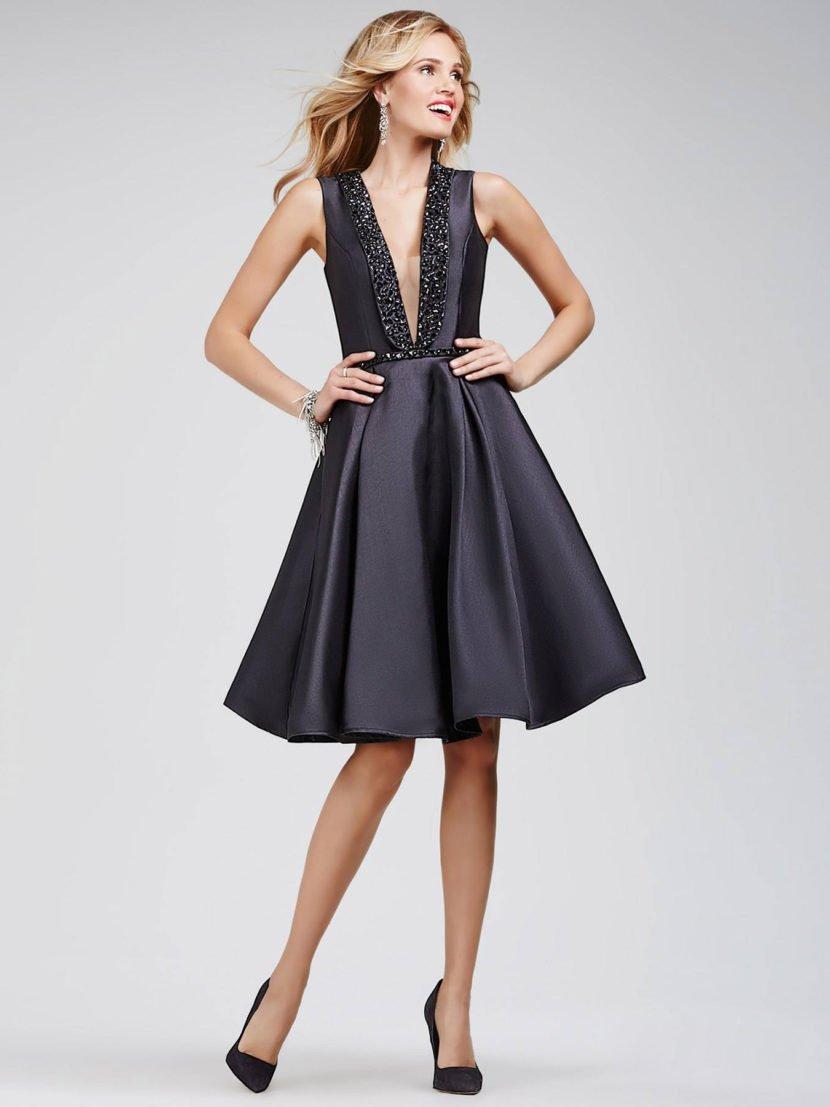 Черное вечернее платье с юбкой А-силуэта до колена и роскошной сверкающей отделкой.