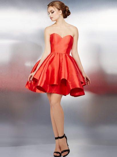 Изысканное вечернее платье привлекает внимание страстным алым оттенком ткани. Усилить впечатление помогает глянцевая фактура и соблазнительный крой с пышной юбкой длиной до середины бедра, покрытой оборками. Чувственный лиф в форме сердечка безупречно вписывается в созданный платьем яркий женственный образ.