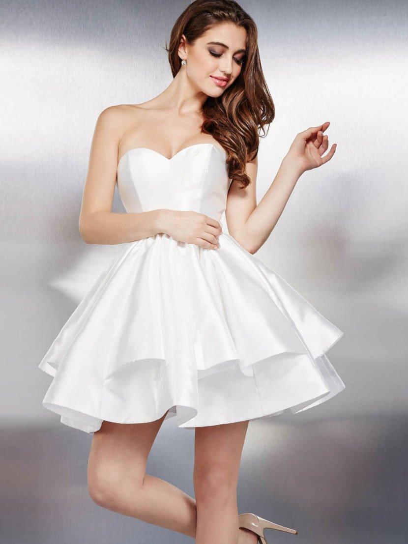 Белое вечернее платье с открытым лифом и пышной юбкой длиной до середины бедра.