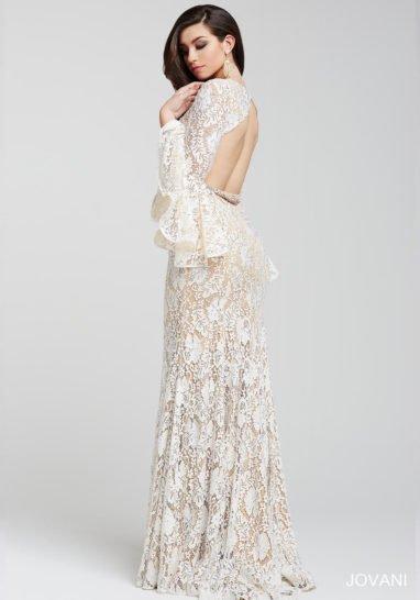 Кружевное вечернее платье на бежевой подкладке с длинными рукавами, украшенными оборками.