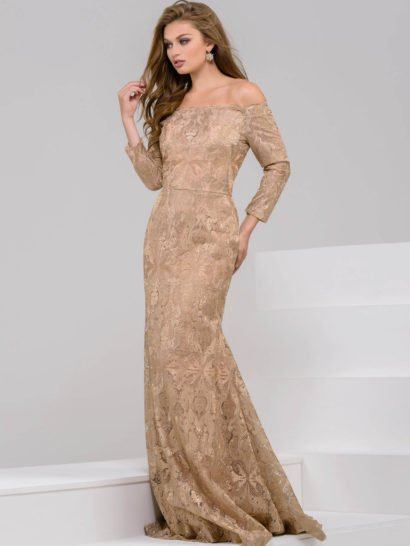 Потрясающее вечернее платье золотистого цвета, оформленное плотной кружевной тканью. Ключевым элементом является портретное декольте, обнажающее плечи и дополненное длинным рукавом прямого кроя. Юбка слегка расклешена в нижней половине подола и образует сзади легкий романтичный шлейф из кружева.