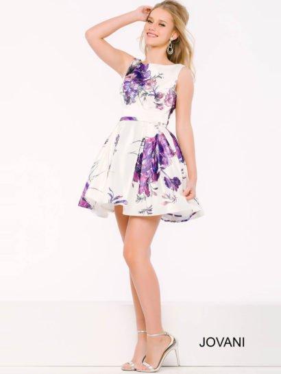 Романтичное вечернее платье, гармонично сочетающее закрытый лиф с вырезом под горло и юбку длиной до середины бедра. Дополняет нежное настроение образа цветочный рисунок в фиолетовых тонах, украшающий белоснежную ткань платья по всей длине. На талии – элегантный узкий пояс. Спинка дополнена небольшим V-образным вырезом.