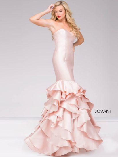 Кокетливое вечернее платье из атласной ткани очаровывает нежным розовым оттенком ткани. Он обеспечит вам уверенность в своей женственности на протяжении всего вечера, а поможет укрепить это чувство облегающий крой с эффектным декольте в форме сердечка и юбкой «русалка», очертания которой подчеркивают многочисленные оборки, спускающиеся по диагонали.