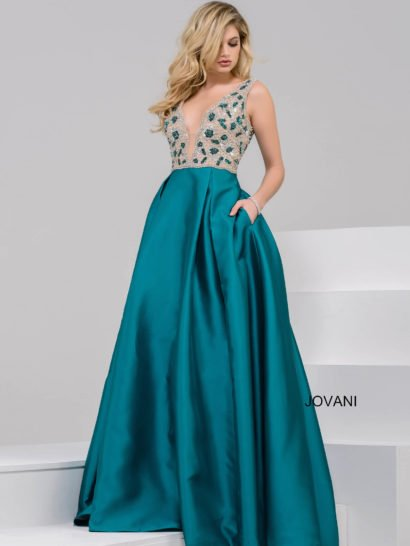 Вечернее платье с роскошной атласной юбкой притягивает внимание благородным оттенком бирюзового. Он прекрасен во всей лаконичности юбки, спускающейся вертикальными волнами. Верх оформлен с иллюзией полупрозрачности и украшен вышивкой в тон подола. Его глубокий V-образный вырез с тонкой вставкой очень чувственно подчеркивает фигуру обладательницы наряда.