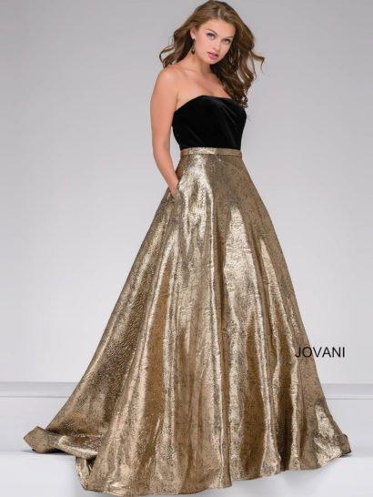 Открытое вечернее платье А-силуэта женственно обрисовывает фигуру и создает безупречно торжественный вид. Драгоценный блеск юбки с золотистой фактурой притягивает все внимание и позволяет обойтись без дополнительных деталей кроя. Открытый верх с прямой линией декольте выполнен из черной бархатной ткани, которая образует с фактурой подола элегантный и притягательный контраст.