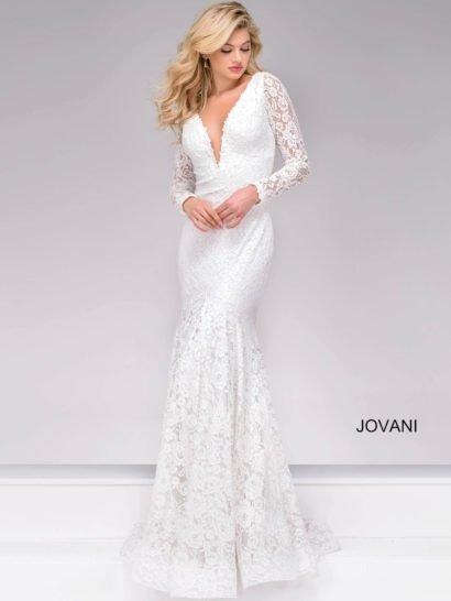Облегающее вечернее платье с силуэтом «рыбка» по всей длине покрыто кружевной тканью с цветочным рисунком, обеспечивающей особенно женственное настроение образа.  Глубокий V-образный вырез уравновешен длинными рукавами.  На спинке – еще более глубокое декольте такой же формы. Юбку завершает небольшой шлейф из кружевной ткани.  Белый цвет ткани делает образ стильным и романтичным.