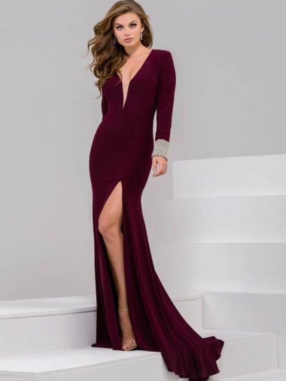 Облегающее вечернее платье полно соблазнительности. Это настроение помогают создать и глубокий бордовый оттенок ткани, и такие детали кроя, как высокий разрез сбоку по подолу или глубокий V-образный вырез, оформленный для комфорта тонкой полупрозрачной вставкой. Стильными дополнениями образа становятся открытая спинка и широкие манжеты, украшенные серебристым бисером.