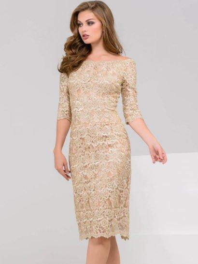 Изысканное вечернее платье с прямой юбкой до колена, выполненное в золотистых тонах. По всей длине платье покрыто слоем фактурного кружева с крупным цветочным узором, кажущегося прозрачным благодаря бежевой подкладке. Открытые плечи, деликатное декольте и рукава длиной до локтя красиво дополняют образ, как и небольшой разрез на юбке сзади.