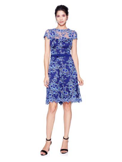 Классическое коктейльное платье фиолетово-голубого оттенка полностью покрыто крупными цветками ириса.  Рукава-крылышки, вырез под горло и традиционная полупрозрачная вставка над декольте идеально украшают образ.  Юбка в сочетании с выразительным поясом, украшенным бантом, без подчеркнутых усилий акцентируют все изгибы фигуры, придавая ей идеальный вид.
