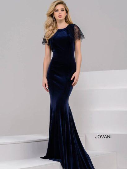 Станьте звездой вечера в сногсшибательном вечернем платье из темно-синего бархата! Эффектная ткань создает не менее впечатляющий облегающий силуэт с юбкой «русалка», дополненной шлейфом. Закрытый верх с округлым вырезом дополняют короткие рукава из черной кружевной ткани. На спинке платья располагается глубокий V-образный вырез декольте.