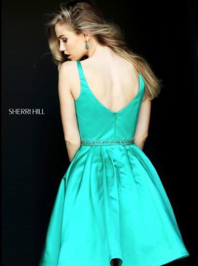 Изумрудное вечернее платье с глубоким вырезом и короткой юбкой А-силуэта.