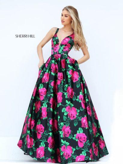 Пышное вечернее платье притягивает взгляды смелым принтом. Крупные малиновые цветы с зелеными листьями покрывают глянцевый черный фон.  Женственный крой А-силуэта универсально подходит любой фигуре. Юбка мягко очерчивает бедра, а глубокое декольте с симметричными узкими бретелями украшает тонкая полупрозрачная вставка. По верху подола располагаются скрытые карманы.