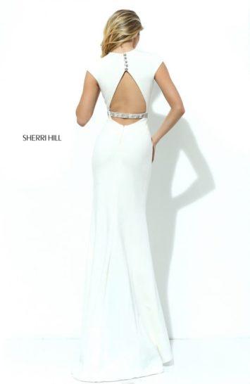Белое вечернее платье облегающего кроя с коротким рукавом и серебристым поясом на талии.