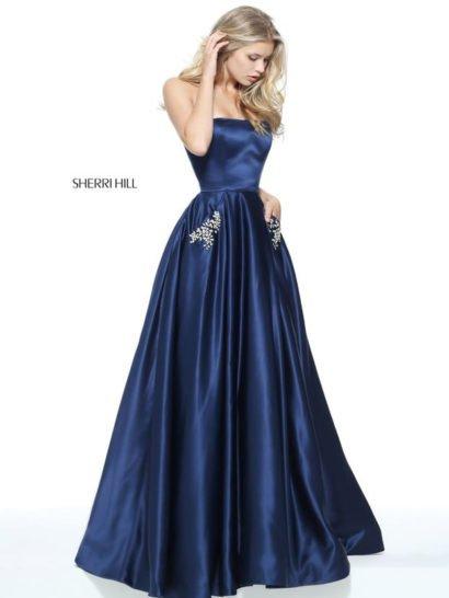 Лаконичное и вместе с тем эффектное вечернее платье сделает обладательницу центром внимания. Роскошная атласная ткань глубокого синего цвета смотрится торжественно и стильно.  Область декольте очерчена прямой линией лифа. Юбка А-силуэта спускается крупными вертикальными складками. Сверху ее украшают скрытые карманы, декорированные серебристой вышивкой.