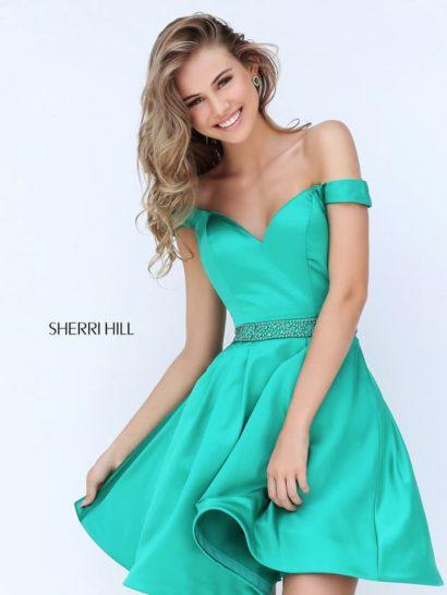 Короткое и яркое вечернее платье идеально подходит для создания образа на выпускной.  Сияющий изумрудный оттенок придает платью индивидуальность, а дополнить его помогает широкий сверкающий пояс, оформленный бисером.  Открытое декольте с приспущенными бретелями выполнено в форме сердечка.  Стильная атласная юбка А-силуэта скрывает ноги лишь до середины бедра.