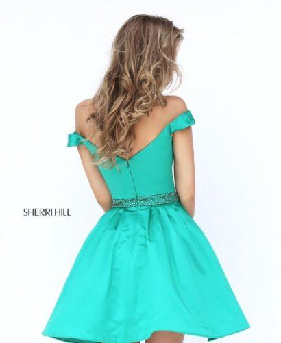 Короткое вечернее платье изумрудного цвета с глубоким декольте и пышной юбкой.