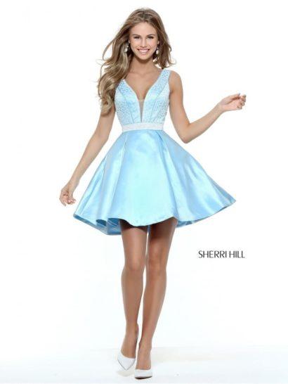 Короткое вечернее платье поможет произвести неизгладимое впечатление на окружающих.  В первую очередь, привлекает внимание освежающий голубой оттенок, прекрасно дополняющий сияющую фактуру атласа.  Самой выразительной чертой кроя служит глубокий V-образный вырез, дополненный вставкой и оформленный по краю элегантной бисерной вышивкой.