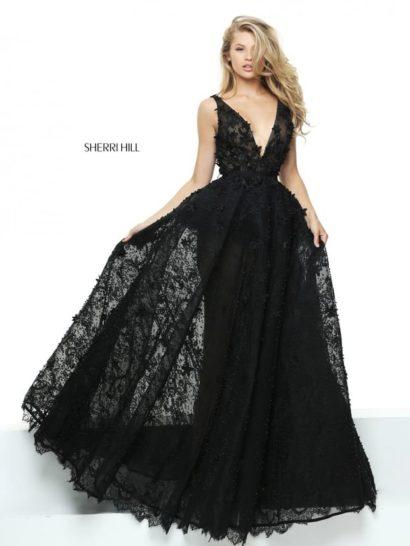 Драматичное вечернее платье черного цвета – для самых изысканных девушек. Прямой силуэт кажется выразительнее благодаря тому, что юбка по всей длине покрыта полупрозрачной тканью.  Верх с узким поясом украшен небольшими цветочными аппликациями. Эффектный образ дополняет глубокое V-образное декольте с симметричными бретелями.
