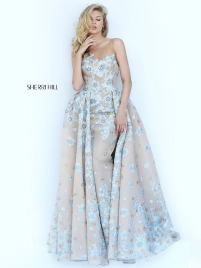 Потрясающее вечернее платье для самых элегантных и ярких девушек! Нежный бежевый оттенок ткани становится деликатной основой для глянцевой голубой отделки. Аппликации покрывают платье по всей длине.  Прямой крой стильно подчеркивает фигуру. Акценты сделаны на декольте, открытом прямым лифом, и на талии, подчеркнутой складками верхней юбки.