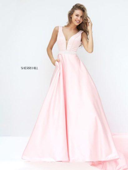 Восхитительное вечернее платье А-силуэта позволит создать торжественный образ. Пастельный розовый оттенок ткани прекрасно сочетается с глянцевой фактурой. Лаконичная отделка представлена лишь узким фактурным поясом.  Лиф с глубоким декольте дополняет вставка под тон кожи. На спинке располагается еще более впечатляющий V-образный вырез.