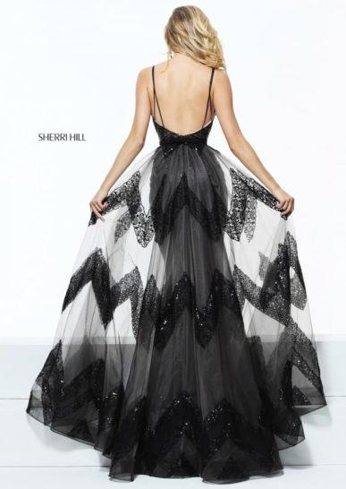Черное вечернее платье с пышной верхней юбкой, глубоким вырезом и блестящей отделкой.