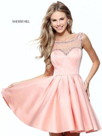Короткое вечернее платье выполнено в актуальном оттенке розовых румян. Стильная пышная юбка длиной до середины бедра позволяет подчеркнуть ноги и сделать образ кокетливым. Украшающие ее вертикальные складки усиливают эффект.  Выразительное декольте в форме сердца украшено полупрозрачной вставкой, декорированной сверкающим бисером. По краю лифа и по линии шеи декор образует объемную полосу.