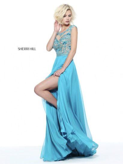 Полное романтичного настроения вечернее платье прекрасно подойдет для выпускного. Свежий голубой оттенок ткани красиво сочетается с бежевым на закрытом лифе с иллюзией прозрачности. В роли отделки лифа – сияющие пайетки.  Прямая юбка в пол выполнена из нескольких легких слоев шифона. Ее смелым украшением является высокий разрез сбоку по подолу, позволяющий продемонстрировать ноги.