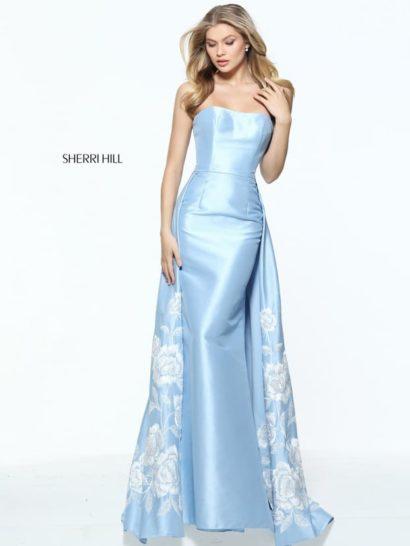 Великолепное вечернее платье из голубого атласа с изысканным прямым декольте.  Привлекает внимание необычный крой юбки.  Ее украшает дополнительный верх, создающий потрясающую альтернативу классическому шлейфу.  Акцентировать оригинальное решение помогает романтичная вышивка, выполненная белой нитью.  Она покрывает верхнюю юбку крупным цветочным узором.