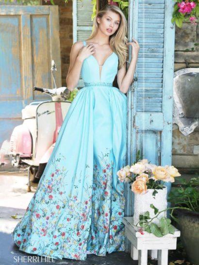 Потрясающе пышное вечернее платье голубого цвета очаровывает многоцветным рисунком по нижней половине подола. Цветочный узор придает юбке дополнительный объем и наполняет весь образ женственностью и нежностью.  Верх оформлен более лаконично, его украшает лишь глубокое декольте с вставкой в тон кожи. Линию талии выделяет узкий пояс, украшенный горизонтальной полоской стразов.