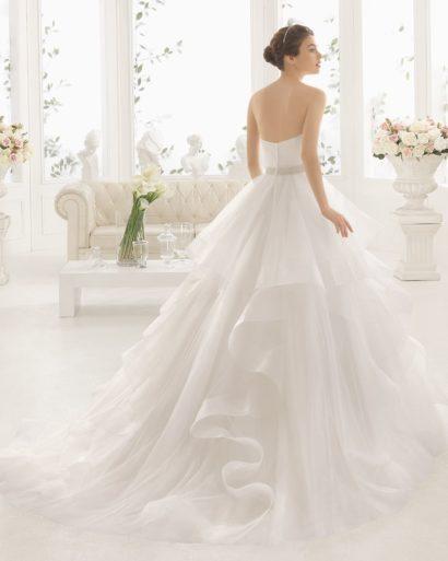 Роскошное свадебное платье с открытым верхом и пышной юбкой сложного кроя.