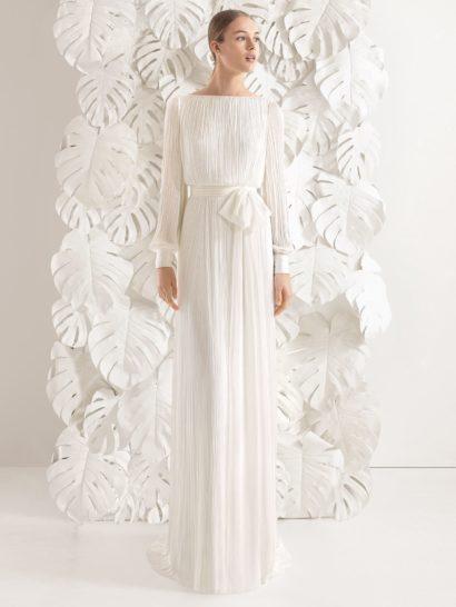 Изысканное свадебное платье создано из легкой ткани с жатой фактурой, придающей силуэту особенную красоту и динамичность.  Сдержанность лифа с вырезом бато и длинными рукавами прямого кроя гармонично сочетается со смелым V-образным декольте, обнажающим спину.  Акцентом в прямом силуэте становится линия талии, выделенная широким поясом, который сбоку украшен нарочито небрежным бантом.  Юбку завершает короткий шлейф.