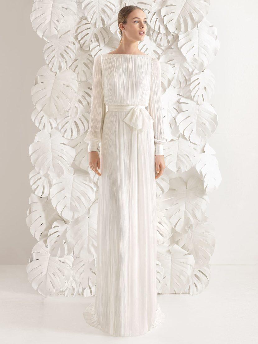 Прямое свадебное платье с широким поясом, длинным рукавом и глубоким вырезом на спине.