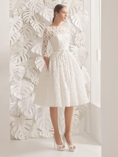 Впечатляющее свадебное платье привлекает внимание неклассической длиной – пышная юбка спускается лишь чуть ниже колена. Второй оригинальной деталью является отделка гипюром с крупным цветочным рисунком, использованная по всей длине.  Верх с вырезом бато дополняют облегающие полупрозрачные рукава длиной три четверти. На талии – узкий пояс с небольшим бантом. Юбка стильно дополнена скрытыми карманами.