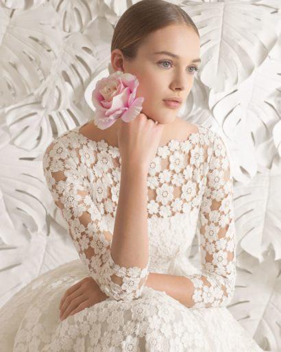Короткое свадебное платье с длинным кружевным рукавом и пышной юбкой с карманами.