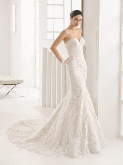 В открытом свадебном платье, обрисовывающем каждый изгиб фигуры, вы покорите сердца всех. Женственная линия декольте и силуэт «русалка» - беспроигрышный дуэт, который украсит вашу фигуру наилучшим образом.  Традиционный кружевной декор хорошо вписывается в настроение свадебного платья и придает юбке с небольшим шлейфом сзади дополнительные воздушность и легкость.