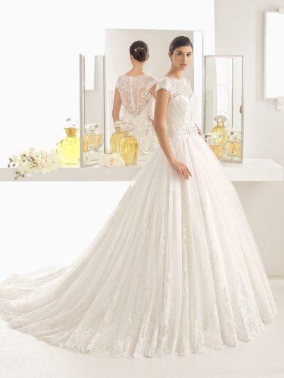 Изысканное воплощение классического кроя «принцесса», это свадебное платье наполнено торжественной атмосферой.  Верх с коротким кружевным рукавом и вырезом под горло смотрится предельно элегантно.  Чуть более откровенной выглядит спинка, покрытая тонкой кружевной тканью и дополненная рядом пуговиц.  Широкий пояс с объемной отделкой спереди сзади украшен бантом.  Многослойная юбка с кружевными аппликациями дополнена длинным шлейфом.