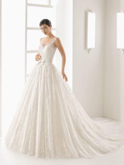 Чувственное и невероятно красивое свадебное платье обрисовывает силуэт с женственным кроем.  Подчеркнуть его помогает пышный полукруг шлейфа, прекрасно дополняющий юбку.  На талии – узкий пояс с кокетливым бантом.  Открытый лиф дополнен узкими кружевными бретелями.  Спинка оформлена тонкой тканью с рядом белых пуговиц.